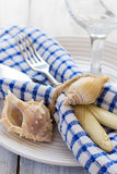 Summer marine style table setting, closeup. Summer table setting with sea decor on a white boards background Royalty Free Stock Photo