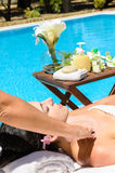 Summer massage at pool. Woman receives massage in spa club near pool in summer Royalty Free Stock Image