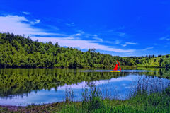 Summer meadow  sailing with forest reflection Stock Photos