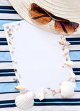 Summer memories. Background with a hat, sunglasses, sea textile, seashells and sheet of blank paper Stock Image