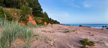 Summer midnight landscape on Baltic sea shore with stones, red r. Ocks, sand and grass. White night at a beach Royalty Free Stock Photos