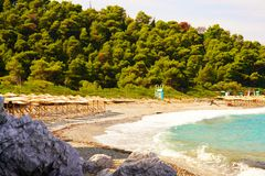 Sun umbrella and beds at Milia beach, Skopelos, Greece stock image