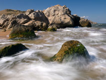 Summer mist waves on the sea. Mist waves and surf on the summer sea against blue sky and rock Royalty Free Stock Image