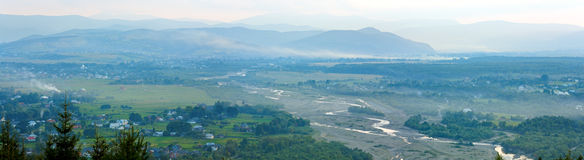 Summer misty morning mountain village panorama Stock Images