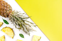 Summer mockup with pineapple on yellow and white background top view Stock Photos