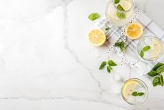 Summer mojito or lemonade. Summer refreshing drinks, mojito or lemonade with fresh mint, slices of lemon, ice, on a light background. copy space top view royalty free stock photo