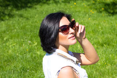 Summer mood. Portrait of a woman in sunglasses on a background of green grass Royalty Free Stock Images