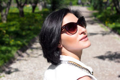 Summer mood. Portrait of a woman in sunglasses at the park Royalty Free Stock Image