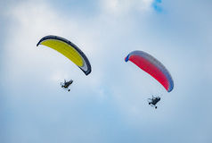 Summer mood: two pilots the paraglider on the blue sky background. Royalty Free Stock Photos