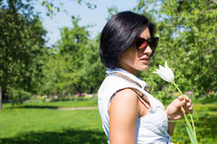 Summer mood. Woman with flowers. Portrait of a woman with white tulip in sunglasses Stock Image