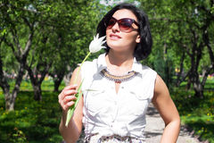 Summer mood. Woman with flowers. Portrait of a woman with white tulip in sunglasses Royalty Free Stock Photography