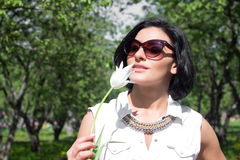 Summer mood. Woman with flowers. Portrait of a woman with white tulip in sunglasses Stock Photos
