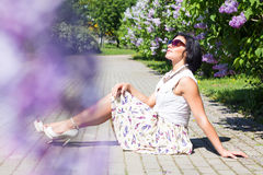 Summer mood. Woman with flowers. A woman is sitting on the pavement among the lilacs Stock Images