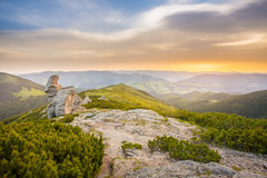 Summer morning mountain landscape. Rocky mountains under cloudy sky . Rocky mountains under cloudy sky filled with golden light of sunset. Summer mountain Royalty Free Stock Photography
