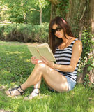 Summer morning reading. Woman reading an exciting book Royalty Free Stock Photos