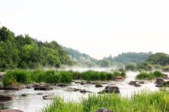Summer morning on the river. Summer sunrise. The fog floats above the river and stones Stock Photography