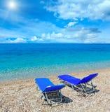 Summer morning sunshiny beach. Summer morning  sunshiny pebbly beach with sunbeds Albania. Two shots stitch high resolution image Stock Photos