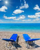 Summer morning sunshiny beach. Summer morning sunshiny beach with sunbeds, white sand and pebble Albania. Two shots stitch high resolution image Royalty Free Stock Photos