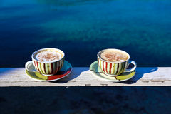 Summer morning two cups of cappuccino with cinnamon on sea background. Stock Photos