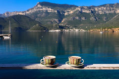 Summer morning two cups of cappuccino on sea background. Summer morning two cups of cappuccino with cinnamon on a background of a seascape and mountains, Greece Stock Photography