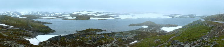 Summer mountain with lake and snow (Norway). Dense fog and summer mountain landscape with lake and snow (Norway, not far Nigardsbreen glacier). Panorama Stock Photo