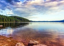 Summer mountain lake theme with cloudy blue sky royalty free stock image
