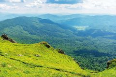 Summer mountain landscape. View from steep grassy slope with rock in to the distant valley. sunny afternoon weather with clouds on the sky stock photography