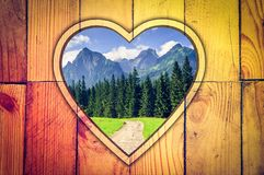 Summer mountain landscape in a wooden frame. Stock Image