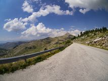 Summer mountain road with clouds royalty free stock photos