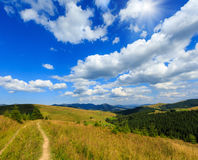 Summer mountain sunshiny view Carpathian, Ukraine. Beautiful blue sunshine sky with white cumulus clouds over summer Carpathian mountain Ukraine, Verkhovyna Royalty Free Stock Photo