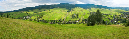 Summer mountain village panorama. Beautiful summer mountain and village on mountainside (Carpathian, Ukraine). Three shots stitch image Stock Photography