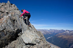 Summer mountaineering. Young woman climbing rocky mountain ridge Royalty Free Stock Images