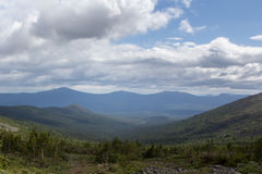 Summer in the mountains. Mountain ranges over the forest. Panoramic view of the mountains. Stock Image