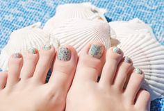 Summer multi color pedicure on female feet. Summer multi color pedicure on female feet, seashells as background royalty free stock photography