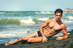 Summer. Muscular guy lying on his side. By the sea. Sculptural body. Stock Photo