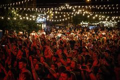 Summer music festival crowd partying outdoor. KIEV-11 JULY,2018: Group of happy music fans partying on summer festival Bazar in bright red lights.Concert crowd stock photo