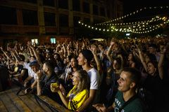 Summer music festival crowd partying outdoor. KIEV-11 JULY,2018: Group of happy young people waving hands on rap concert. Audience on summer music festival Bazar stock image