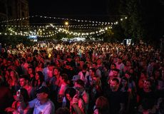 Summer music festival crowd partying outdoor. KIEV-11 JULY,2018: Group of young people listening to musician on stage at outdoor summer festival Bazar. Adult royalty free stock photography