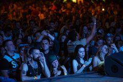 Summer music festival crowd partying outdoor. KIEV-11 JULY,2018: Group of young people listening to music on summer festival at the scene. View from stage on stock photos