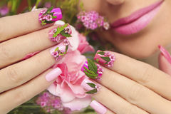 Summer nail design. Multicolored pastel manicure with a design of natural flowers on female hand close up.Summer nail design royalty free stock images