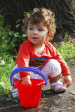 Summer near the river little girl playing with a bucket of water Royalty Free Stock Photos