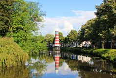 Summer in Netherlands. Canal view with water reflection for the lighthouse royalty free stock photo