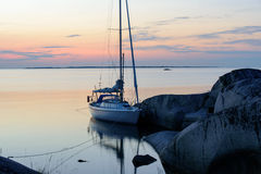 Summer night in the archipelago. Summer night light over a sailboat moored at small rocky islands in the outer part of the archipelago of Stockholm, Sweden royalty free stock photo