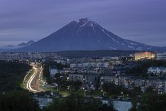 Summer night cityscape driving automobiles on city road on background of volcano royalty free stock images