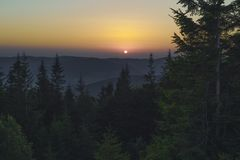 Summer night after sunset in the Carpathians. The sun painted the sky orange. The contours of trees and mountains stand in the dark. Carpathians, Ukraine Royalty Free Stock Images