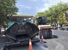 Heavy asphalt paver and road vibrating roller seal ready for repair roads in a modern city. Among the summer noon, a heavy asphalt paver and road vibrating Stock Images