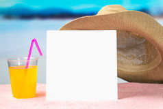 Summer offer background template for promotion and sales. Yellow cocktail and brimmed hat on towel with beautiful paradise view. Stock Images