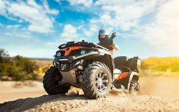 Summer offroad adventure on atv in sand quarry. Male rider in helmet on quad bike in sandpit royalty free stock images