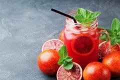 Summer orange lemonade drink or juice decorated mint leaves in mason glass jar on black table. Summer orange lemonade drink or juice decorated mint leaves in Stock Images