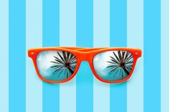 Summer orange sunglasses with palm trees reflections isolated in pastel blue background with stripes Stock Photography